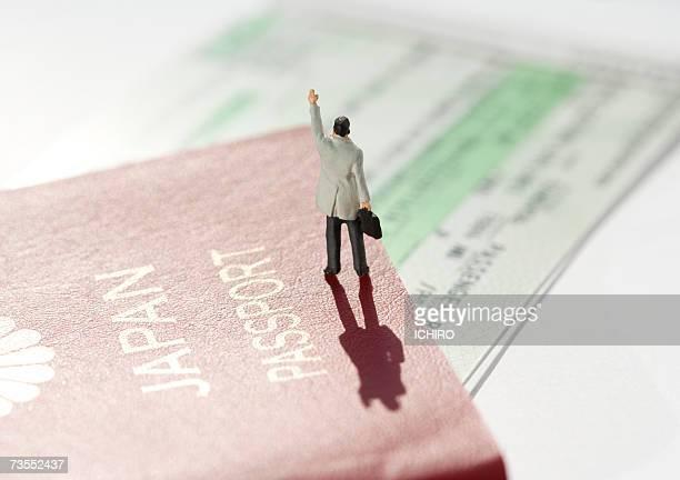 Figurine with passport and plane ticket