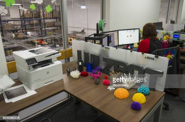 Figurines created with LulzBot 3D printers sit on display in front of signage at the Aleph Objects Inc production facility in Loveland Colorado US on...