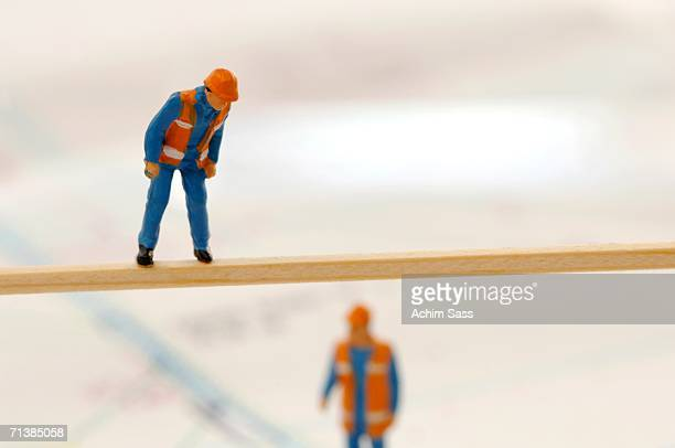 Figurines of construction workers working at construction site, (selective focus)
