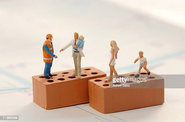 figurines of construction workers and family at construction site - représentation humaine photos et images de collection