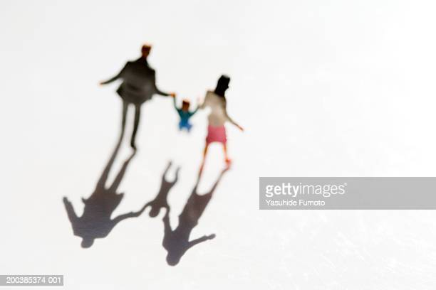 Figurines of family with child on white background, casting shadow