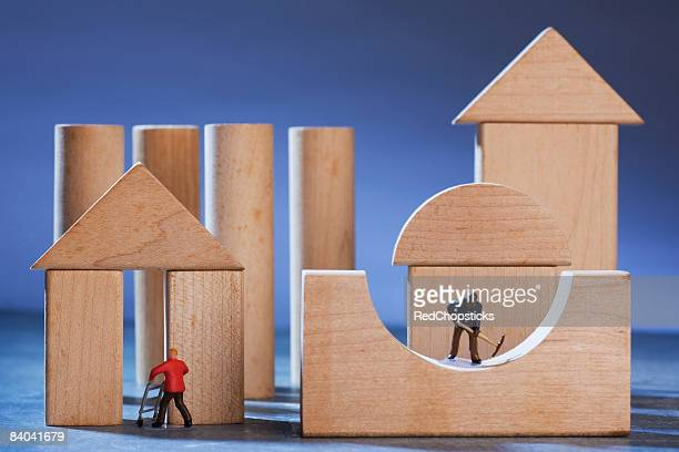 Figurines of manual workers constructing wooden house