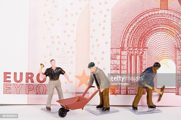 Figurines of manual workers in front of a European union euro note