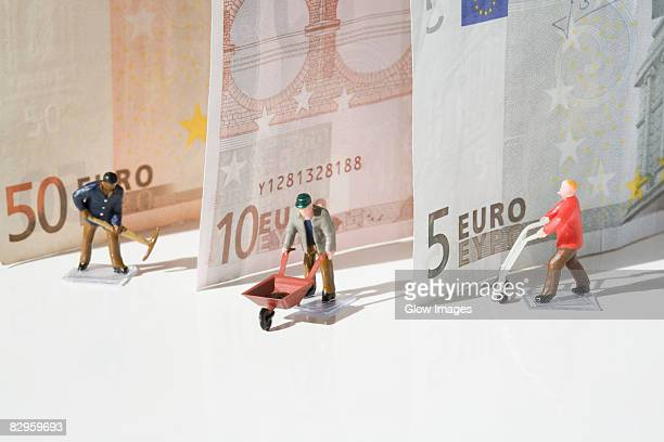 Figurines of manual workers with European union banknotes