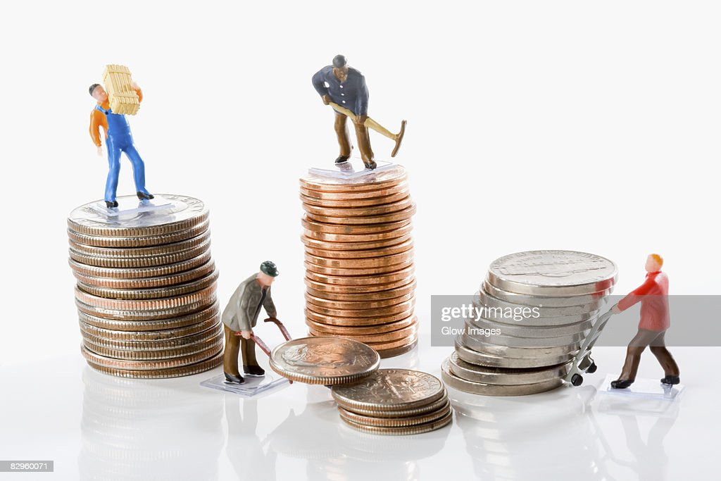Figurines of manual workers with stacks of coins : Stock Photo