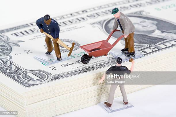 Figurines of manual workers with US paper currency