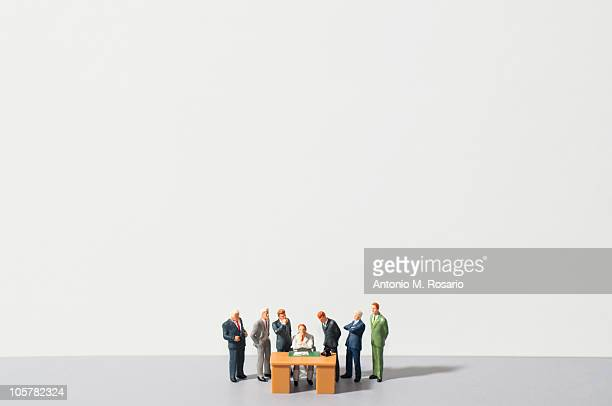 Figurines of people standing around desk