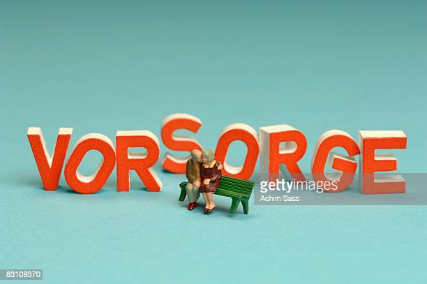 Figurines of senior couple on bench in front word Vorsorge