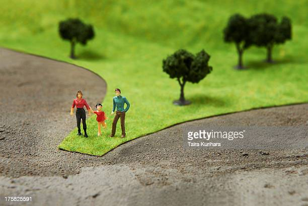 Figurines on pretend grass with trees