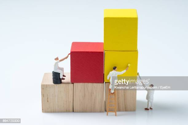Figurines Painting Blocks Against White Background