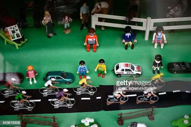 Figurines representing cyclists of the Tour de France are displayed in a shop window in SaintLo Normandy on June 29 three days before the start of...