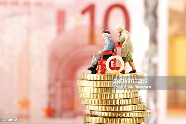 figurines, senior citizens, on pile of coins - social security stock pictures, royalty-free photos & images