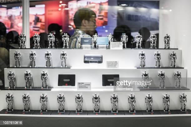 Figurines stand on display next to Samsung Electronics Co solid state drives during the Tokyo Game Show in Chiba Japan on Saturday Sept 22 2018 The...