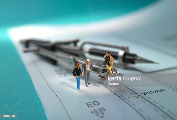 figurines standing on architecture plan - human representation stock pictures, royalty-free photos & images