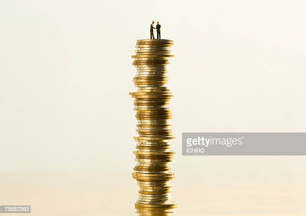 figurines standing on stack of golden coins - dolly golden stock pictures, royalty-free photos & images