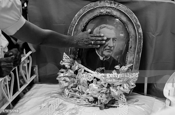 Fiéis tocam a imagem de Padre Cícero colocada sobre a cama onde ele faleceu. Esta e muitos outros objetos que pertenceram ao padre podem ser vistas...
