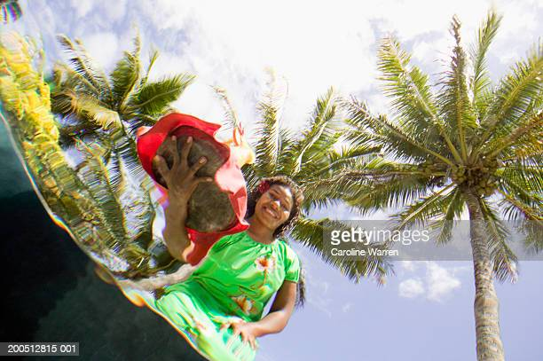 Fiji, Beqa Island, woman serving drinks beside pool, underwater view