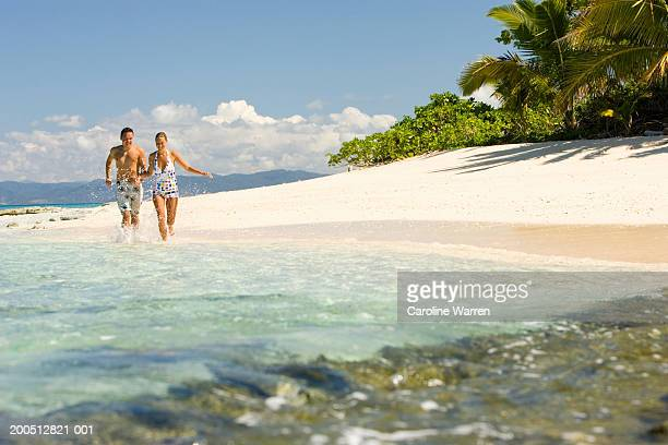Fiji, Beqa Island, young man and woman running along beach