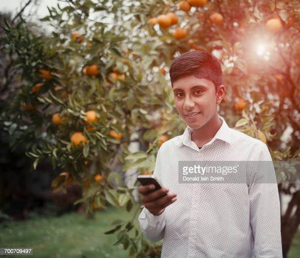 Fiji Indian boy texting on cell phone in orchard