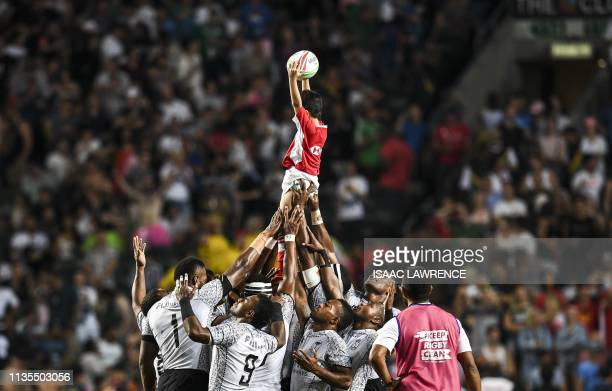 TOPSHOT Fiji lift a ball boy in the air before the start of the Cup final against France on the Third day at the Hong Kong Sevens rugby tournament on...