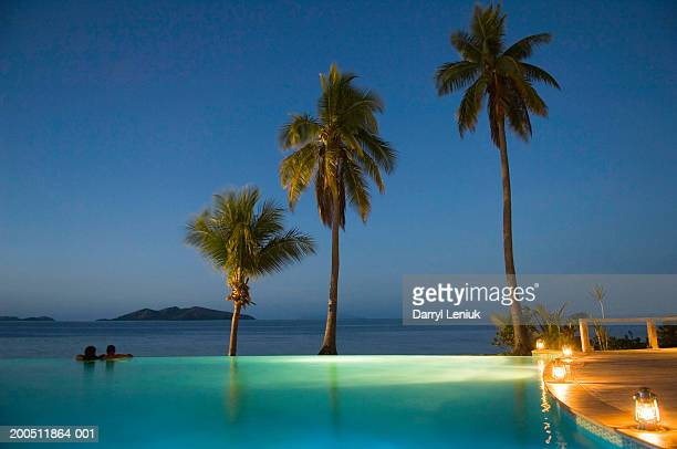 Fiji, man and woman in infinity pool beside sea at dusk, rear view