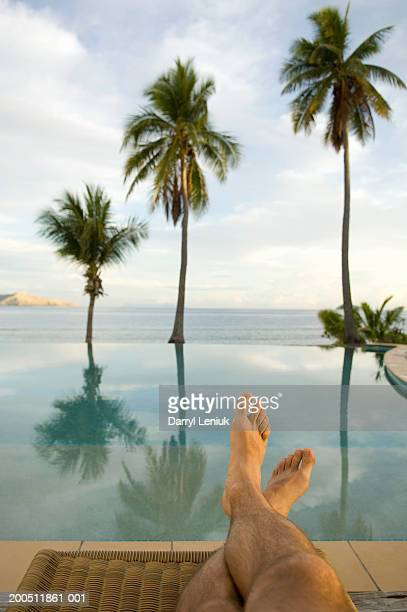 Fiji, man sitting on lounge chair beside infinity pool, low section