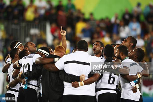 Fiji players and staff huddle as they win gold after the Men's Rugby Sevens Gold medal final match between Fiji and Great Britain on Day 6 of the Rio...