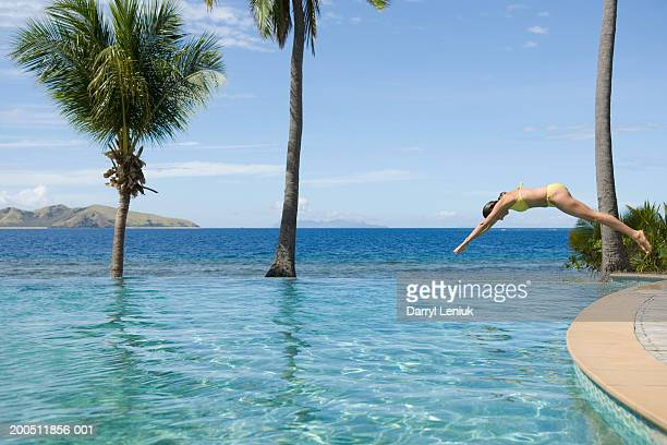Fiji, young woman diving into infinity pool, side view