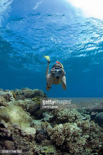 Fiji, young woman snorkeling with underwater camera