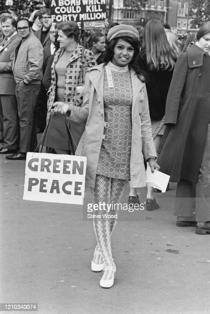 Fijian protestor Sneh Sym wearing patterned leggings and a patterned mini dress carrying a bag on which is written 'green peace' at a CND...