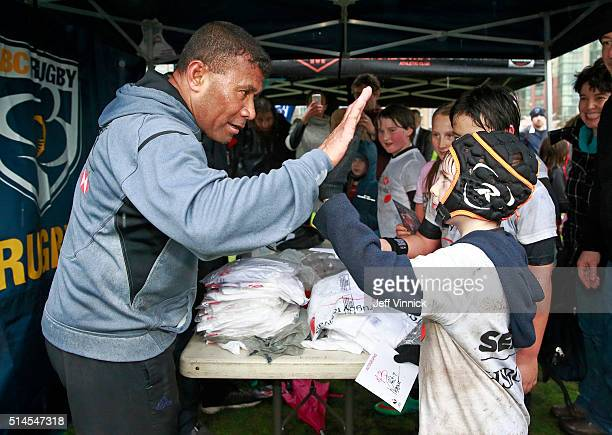 Fijian Sevens rugby legend Waisale Serevi highfives a young rugby player during the HSBC Youth Rugby Festival at David Lam Park March 9 2016 in...