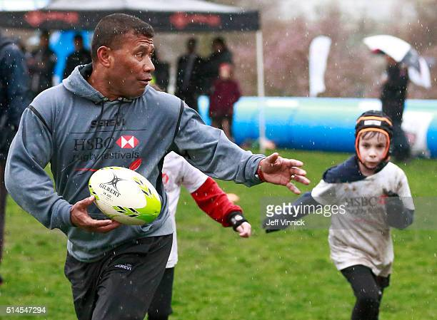 Fijian Sevens rugby legend Waisale Serevi runs away from a young rugby player during the HSBC Youth Rugby Festival at David Lam Park March 9 2016 in...