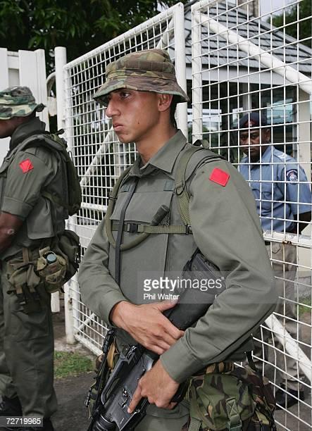 Fijian soldier Meli Bainimarama son of Commander Frank Banimarama secures the entrance to the home of Fijian Prime Minister Laisenia Qarase placing...