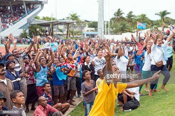TOPSHOT Fijians celebrate the victory of their Sevens rugby team against Britain in the final at the Rio Olympics inside ANZ stadium in Suva on...