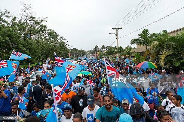 Fijians clad in blue with flags march towards the stadium to celebrate with Fiji rugby sevens team in Suva upon their arrival from Brazil on August...