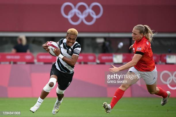 Fiji's Alowesi Nakoci runs past Britain's Alex Matthews to score a try in the women's bronze medal rugby sevens match between Fiji and Britain during...