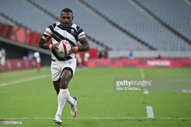 Fiji's Asaeli Tuivuaka runs to score a try in the men's final rugby sevens match between New Zealand and Fiji during the Tokyo 2020 Olympic Games at...