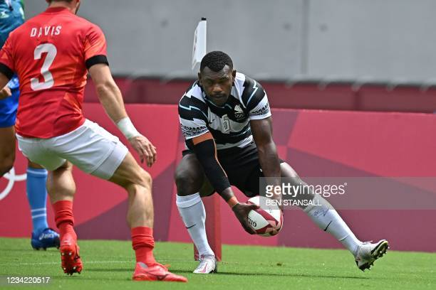 Fiji's Asaeli Tuivuaka scores a try in the men's pool B rugby sevens match between Fiji and Britain during the Tokyo 2020 Olympic Games at the Tokyo...