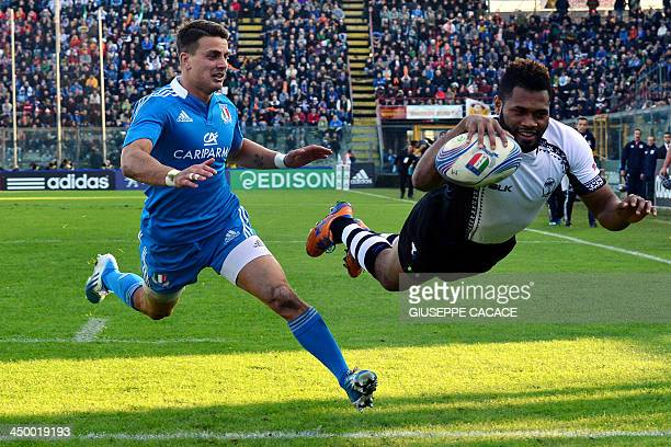 Fiji's fullback Metuisela Talebula jumps to score chased by Italy's Tommaso Iannone during the rugby test match between Italy and Fiji on November 15...