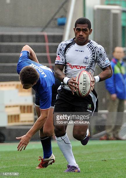 Fiji's Jimilai Naikadawa runs before France's Yoann Laousse during their pool A match in the 2012 Tokyo Sevens World Series rugby tournament in Tokyo...