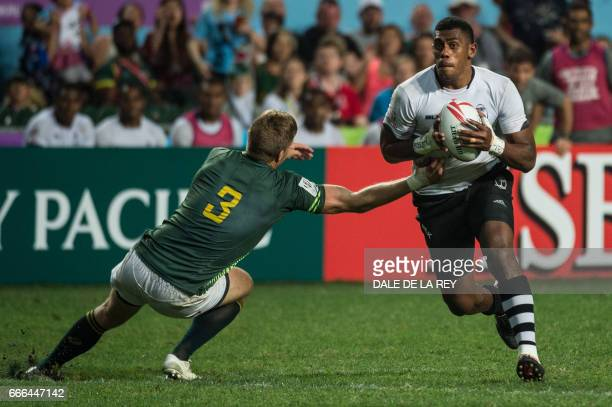 Fiji's Kalione Nasoko is tackled by South Africa's Dylan Sage in the Cup Final on the final day of the Hong Kong Rugby Sevens tournament on April 9...