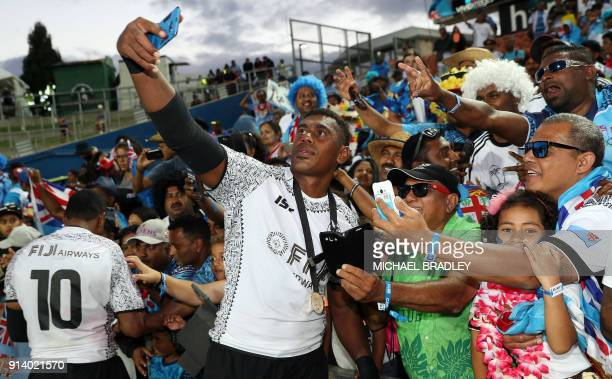 Fiji's Kalione Nasoko takes a selfie with fans as he and his teammates celebrate after winning the final gold medal match at the World Rugby Sevens...