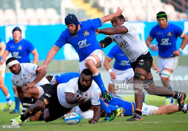 Fiji's lock Leone Nakarawa pushes Italy's lock Dean Budd as Fiji's tighthead prop Manasa Saulo reaches for the ball during a rugby union test match...