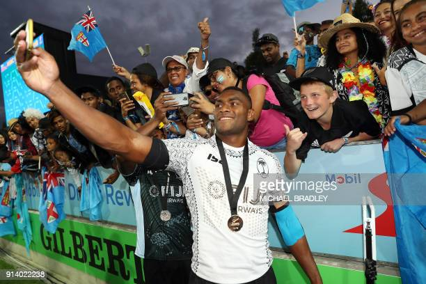 Fiji's Mesulame Kunavula poses with fans to celebrate after winning the final gold medal match at the World Rugby Sevens Series between Fiji and...