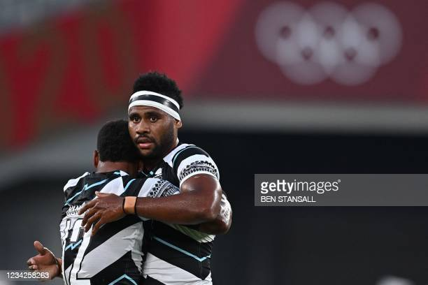 Fiji's Napolioni Bolaca hugs Vilimoni Botitu after winning the men's final rugby sevens match between New Zealand and Fiji during the Tokyo 2020...