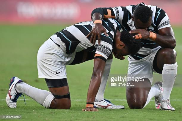 Fiji's Napolioni Bolaca reacts with a teammate after winning the men's final rugby sevens match between New Zealand and Fiji during the Tokyo 2020...