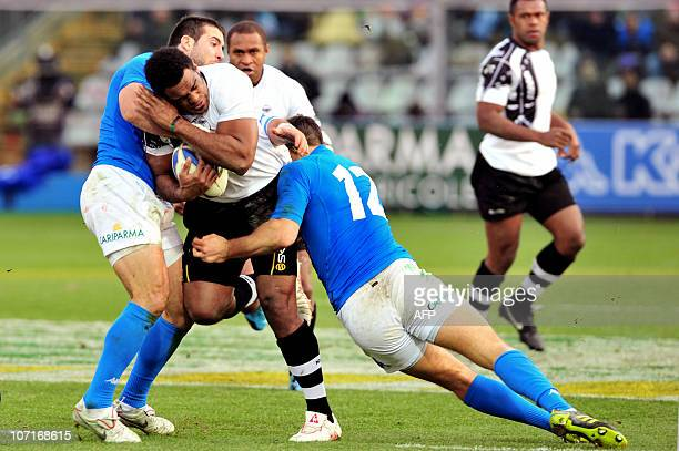Fiji's Napolioni Nalaga vies with Italy's Alberto Sgarbi and Robert Barbieri during the test rugby match between Italy and Fiji on November 27 2010...