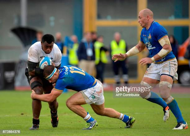 Fiji's number 8 Nemani Nagusa is tackled by Italy's inside centre Tommaso Castello as Italy's number 8 Sergio Parisse looks on during the...