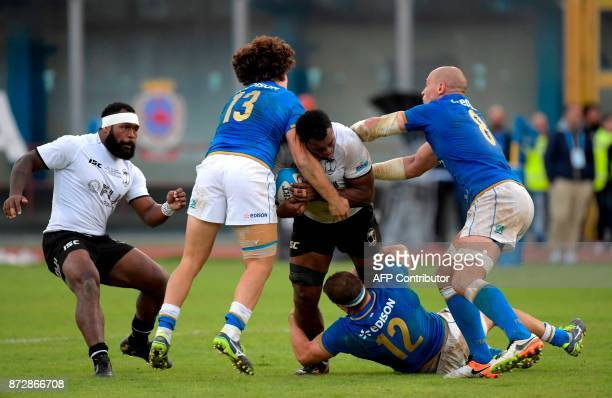 Fiji's number 8 Nemani Nagusa is tackled by Italy's inside centre Tommaso Castello Italy's outside centre Tommaso Boni and Italy's number 8 Sergio...