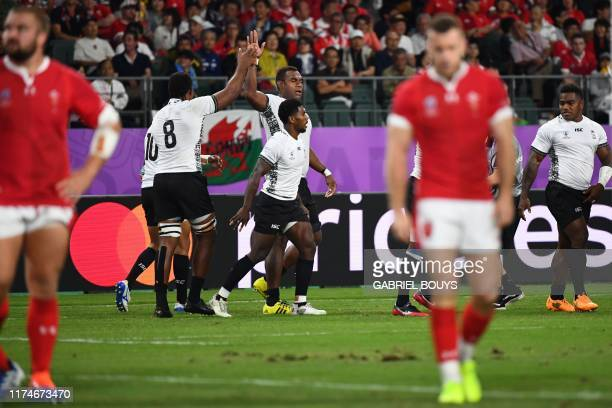 Fiji's players celebrate a try by Fiji's full back Kini Murimurivalu during the Japan 2019 Rugby World Cup Pool D match between Wales and Fiji at the...